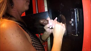 Sultry mature blonde in fishnets jerks off a glory hole cock