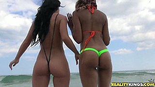 Slutty girls are wearing crotchless bikinis on a public beach