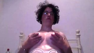 Curly short haired brunette MILF in glasses flashed her oiled big tits