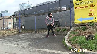 Straight haired emo chick pulls down black jeans to pee at the bus parking