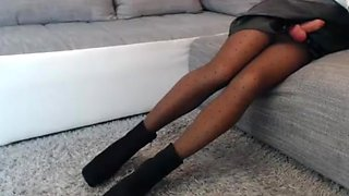 Sexy crossdresser in leather skirt and boots