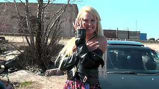 Stunning blonde young babe bends over on the hood of the car